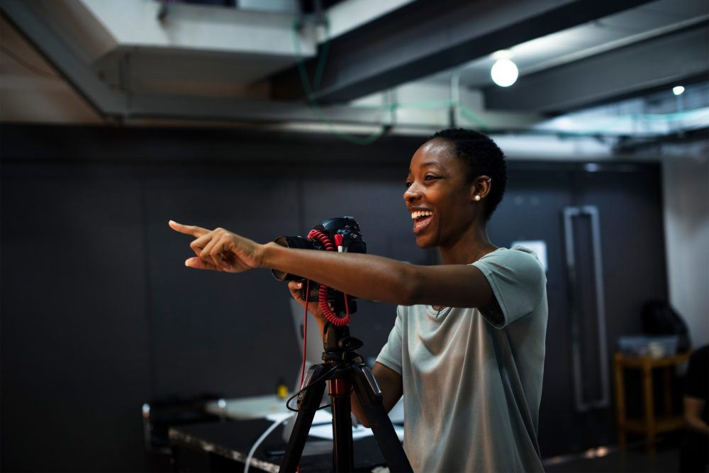 Woman behind the camera pointing