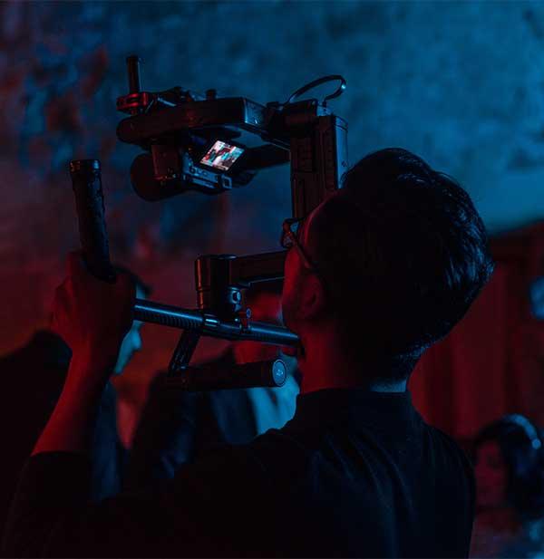 Man holding up camera on dark set